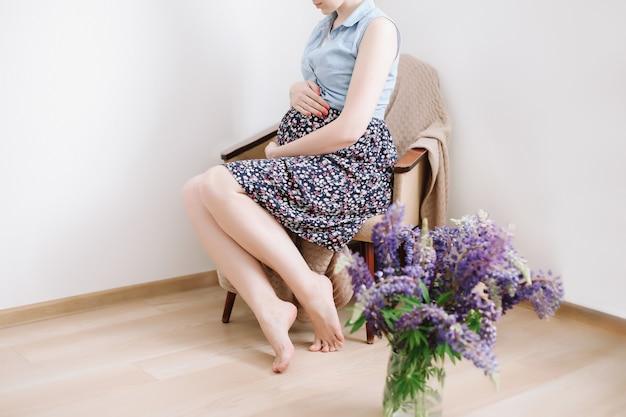 Беременная женщина, сидящая в кресле дома, концепция подготовки и ожидания беременности по беременности и родам