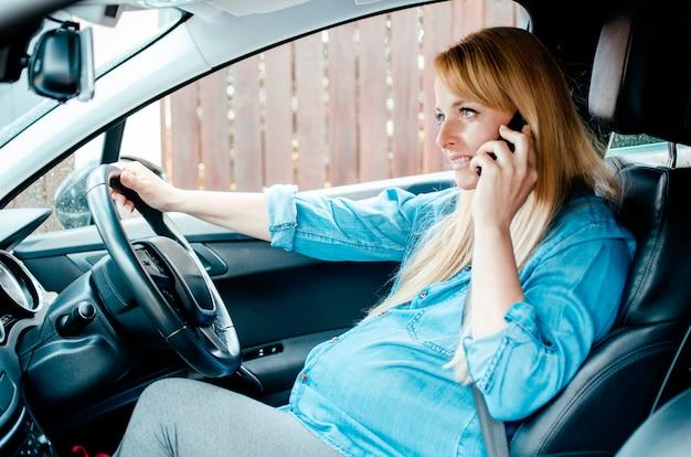 駐車場で携帯電話を使用して車に座っている妊娠中の女性。緊急呼び出しのための運転の一時停止を持つ美しい妊娠中の女性