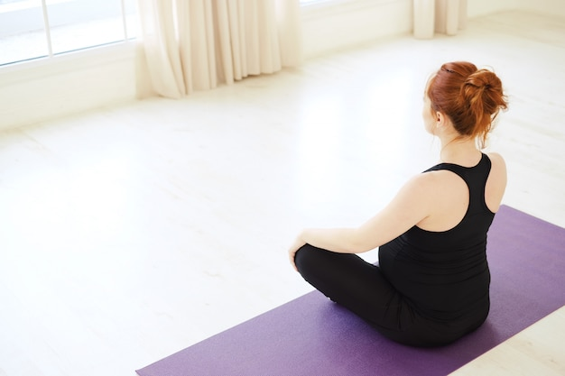 Pregnant woman sitting in lotus pose looking in the window
