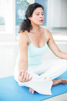 Pregnant woman sitting in lotus pose with eyes closed