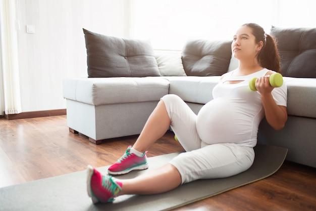 妊娠中の女性が彼女の手でダンベルを持ってヨガマットの上に座って