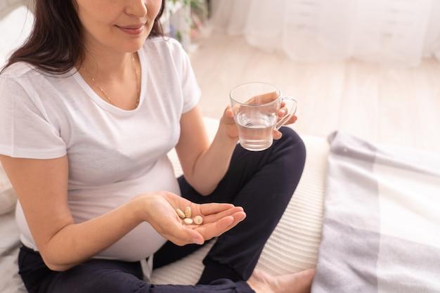 Беременная женщина сидит на кровати и держит стакан питьевой воды и витаминов