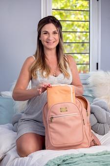 임신 한 여자는 태어날 그녀의 아기의 것들과 함께 배낭을 준비 침대에 앉아