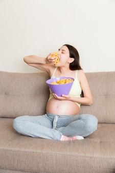 소파에 앉아있는 임산부는 소금에 대한 갈망 때문에 칩을 먹고 있습니다.