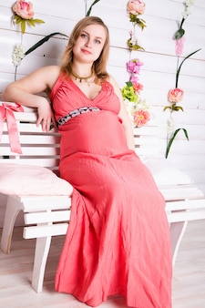 Pregnant woman sitting in the red dress