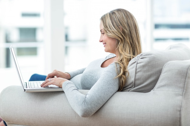 Pregnant woman sitting on sofa and using laptop