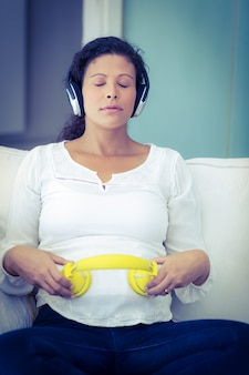 Pregnant woman sitting with eyes closed listening music from headphones on sofa