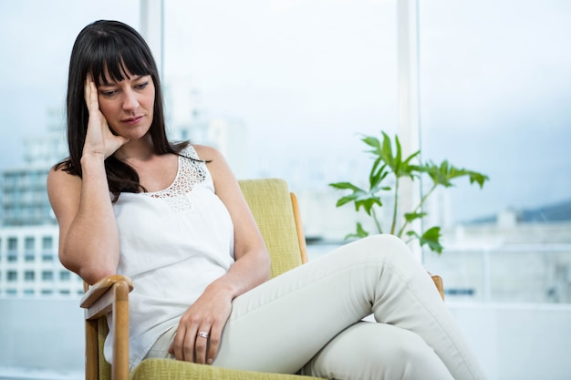 Pregnant woman sitting with headache at home