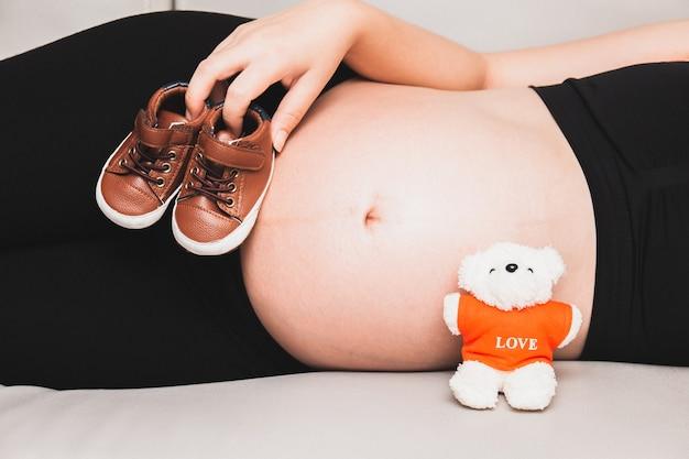 妊娠中の女性は彼女の腹の近くに小さな赤ちゃんの靴を持ってソファと手で寝る