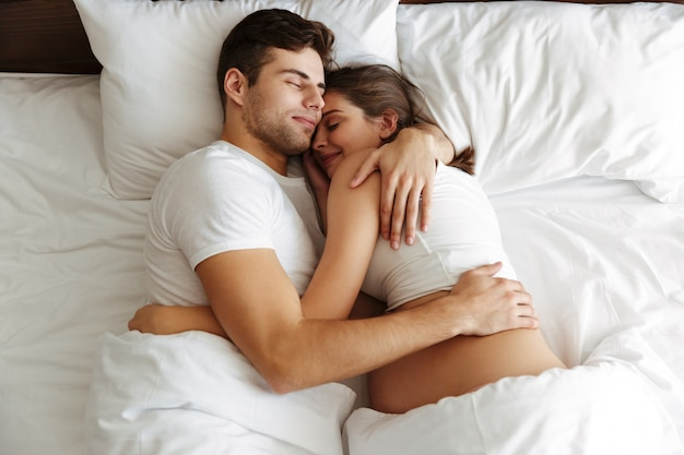 Pregnant woman sleeping in bed with her husband