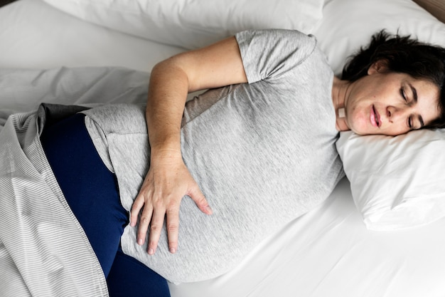 Pregnant woman sleeping on the bed