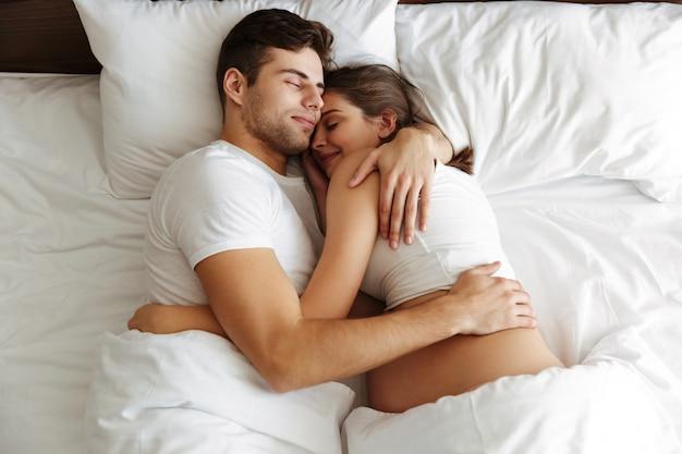 임신 한 여자는 그녀의 남편과 함께 침대에서 자