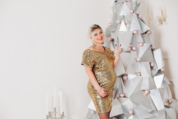 Pregnant woman in sparkling party dress at christmas tree with peace gesture.