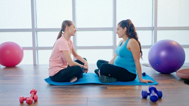 Pregnant woman in a sports class communicates with a young girl