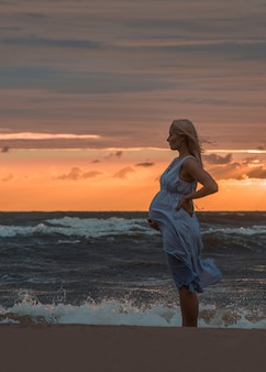 海のビーチに立っている妊娠中の女性