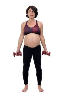 Беременная женщина, делающая упражнения с гантелями на белом