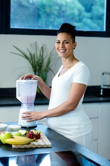 Pregnant woman standing in kitchen and preparing fruit juice in blender