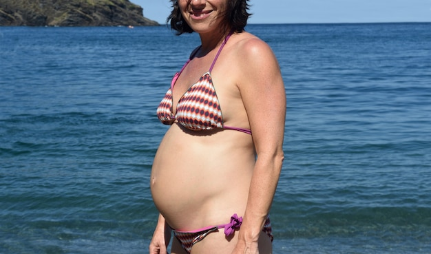 Pregnant woman standing on the sea
