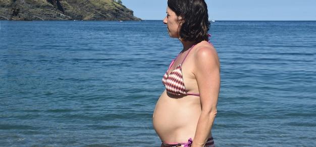 Pregnant woman standing sunbathing on the beach