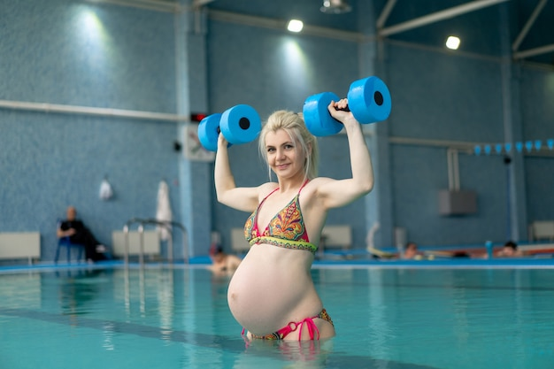 Pregnant woman standing in water with dumbbells indoors swiming pool  active pregnancy sport and fitnes concept helthy lifestyle