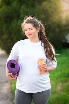 Беременная женщина стоит на природе с циновкой для йоги и бутылкой воды. беременная женщина перед тренировкой