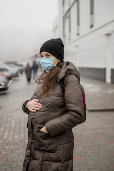 A pregnant woman stands on the street of a european city during an epidemic of coronavirus.