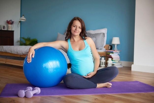 Беременная женщина начинает сеанс йоги