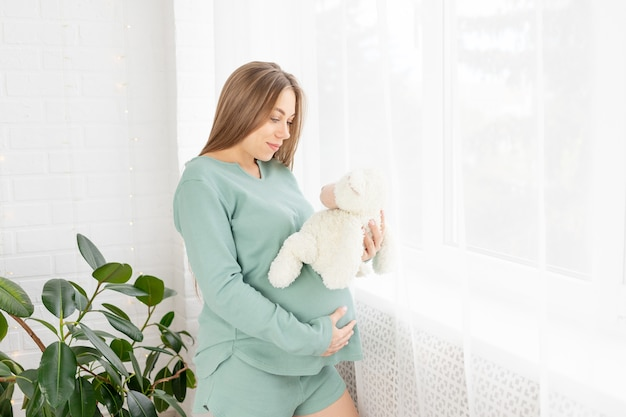 A pregnant woman strokes her big belly standing at the window in the morning with a toy in her hands dreaming of a child, the concept of waiting for a child, love and upbringing