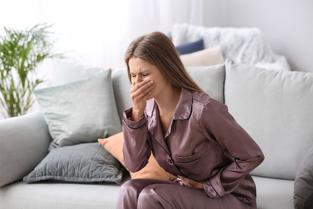 Pregnant woman suffering from toxicosis at home