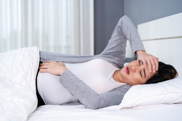 Pregnant woman suffering headache lying in a bed