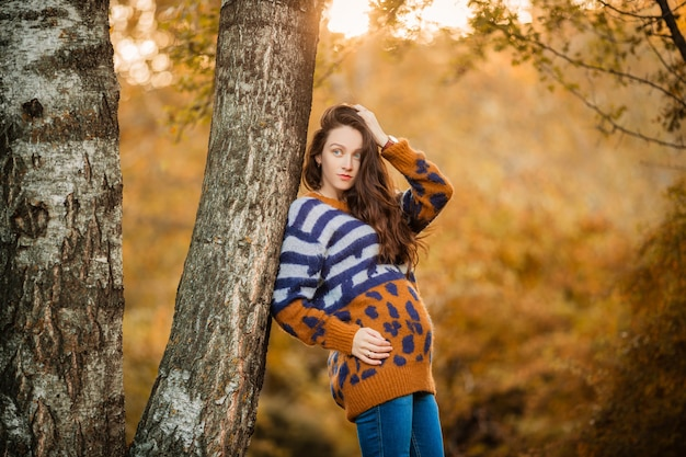 Pregnant woman in sweater in autumn for a walk