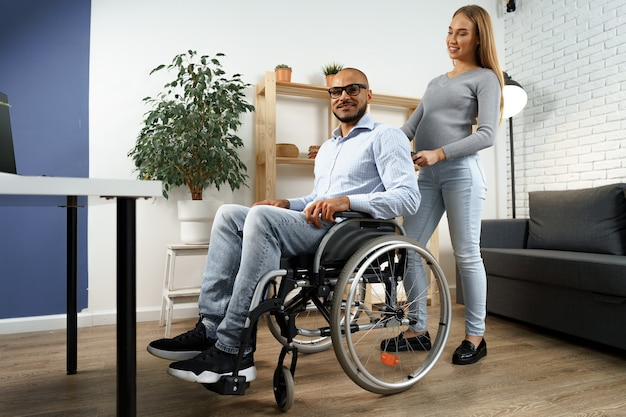 Pregnant woman takes care of her disabled husband in wheelchair