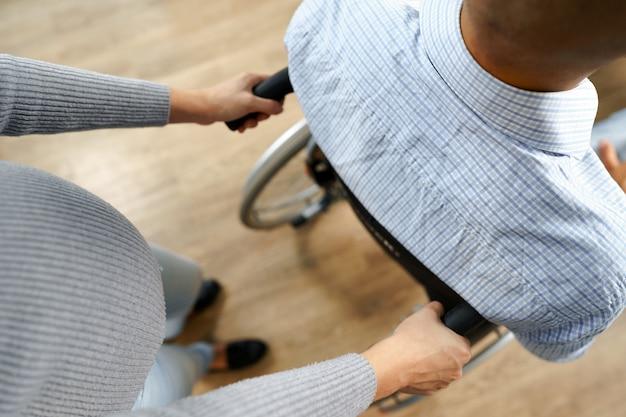 임산부가 휠체어를 탄 장애인 남편을 돌봅니다.