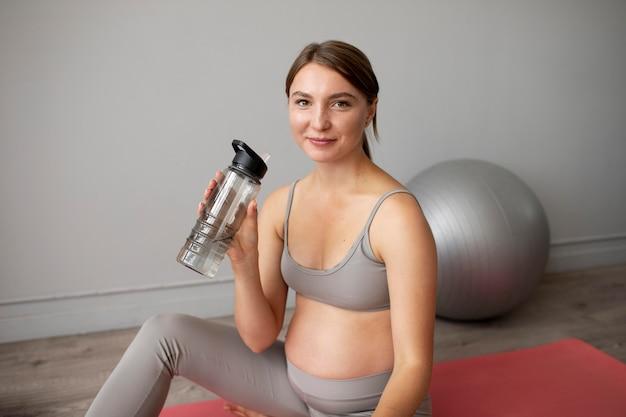 집에서 운동을 하다가 휴식을 취하는 임산부