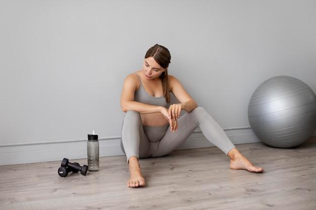 Donna incinta che si prende una pausa dall'esercizio a casa