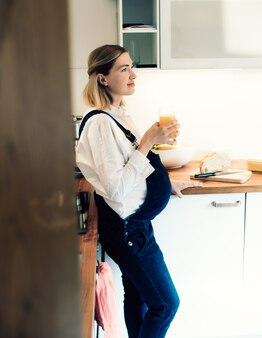 부엌에서 신선한 주스를 복용하는 임신한 여자. 임신한 여자는 부엌에서 주스를 마신다. 배가 임신한 엄마. 아기가 뱃속에 있습니다.