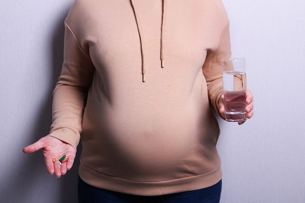 Pregnant woman taking pills during pregnancy. image of pregnancy and maternity.