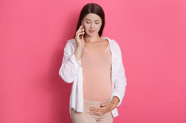 妊娠中の女性が彼女のスマートフォンで話していると触れて、見下ろして、白いシャツを着ています。