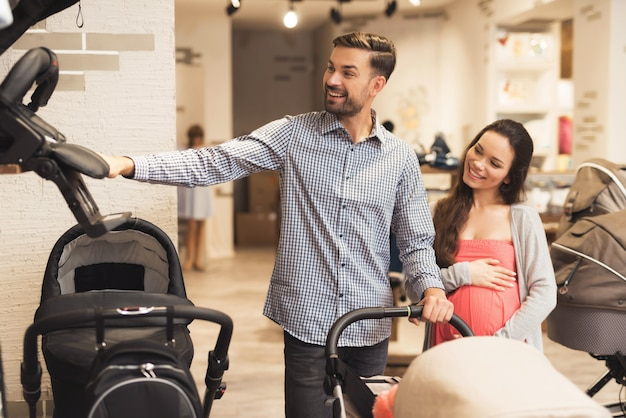 A pregnant woman together with a man choose a baby carriage