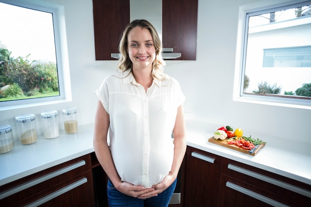 Pregnant woman touching belly in the kitchen