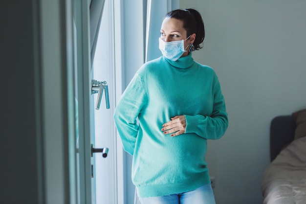 Pregnant woman touching belly and wearing mask