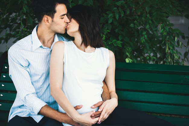 Pregnant woman touching her husband hands