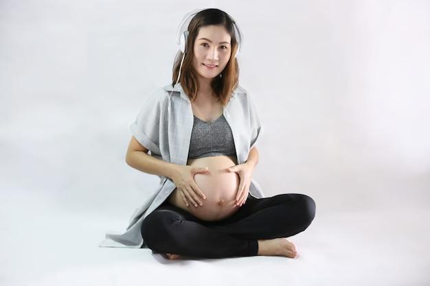 白い背景の上の胃に触れる妊娠中の女性