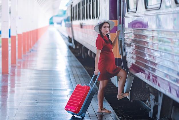 観光客の袋や荷物が付いている鉄道駅で妊婦の観光客。休暇の概念。