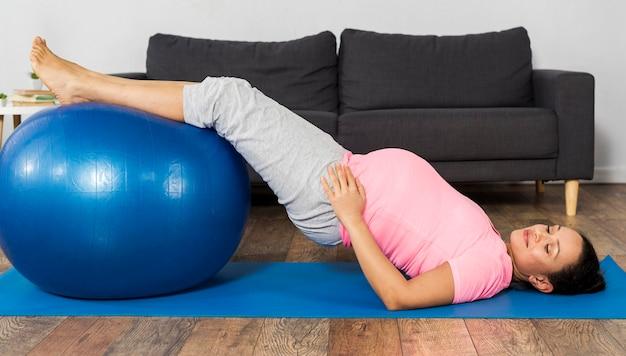 Donna incinta che si allena a casa sul pavimento con la palla