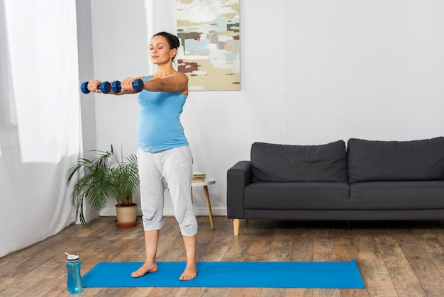 Беременная женщина тренируется с весами дома на тренировочном коврике