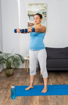 Pregnant woman training with weights at home on mat