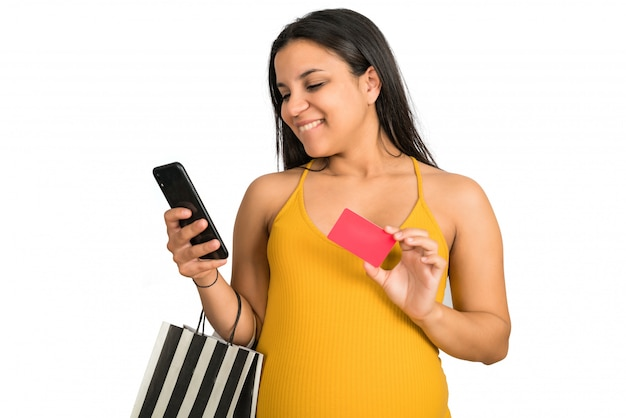 Pregnant woman using credit card and phone to shop online