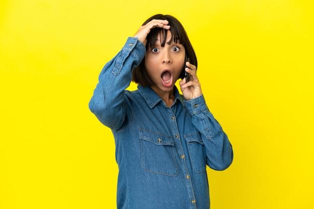 노란색 배경에 격리된 휴대전화를 사용하는 임산부는 옆을 바라보며 깜짝 제스처를 하고 있다