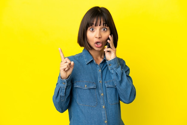 指を持ち上げながら解決策を実現しようとしている黄色の背景に分離された携帯電話を使用して妊娠中の女性